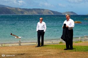 Od prawej: dyrygent Milen Nachev, skrzypek Derek Hensler i nowozelandzka mewa rzucają wyzwanie silnym wiatrom z zatoki  Fitzroy. (fot. tancerz Ben Chen)