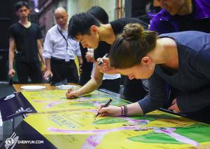 Przed wyjazdem z Melbourne, artyści podpisują dwa plakaty.  (fot. tancerz Ben Chen)