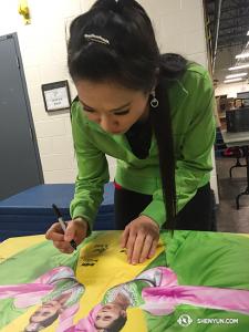 De retour au Canada après la tournée Européenne, la Shen Yun International Company est très occupée à signer l'affiche de cette année comme souvenir. (Photo par la projectionniste Annie Li)