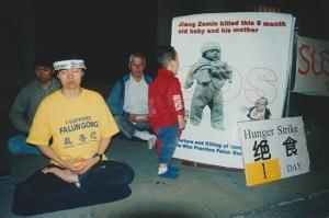 První den protestní hladovky před čínskou ambasádou v Londýně v roce 2001. Benova matka je vlevo vepředu. Malé dítě se dívá na obrázek miminka, které bylo zabito v důsledku pronásledování Falun Gongu v Číně.