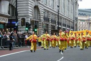 Novoroční londýnský pochod. Ben Chen (vepředu vpravo) a další praktikující Falun Gongu hrají na pásové bubny a spolu s dalšími stovkami skupin pochodují po Piccadilly.