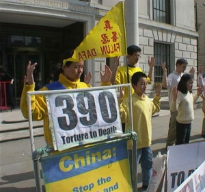 Desetiletý Ben stojí vedle své matky a dalších praktikujících Falun Gongu a společně cvičí před ambasádou. (foto s laskavým svolením Minghui.org)