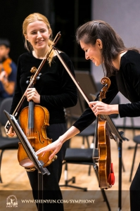 První houslistka Paulina Mazurkiewicz a houslistka Elisabeth Reynolds uvolňují atmosféru před koncertem.