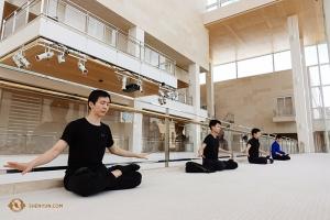 Po sesji treningowej tancerze, między innymi Steve Feng (po lewej) równoważą wcześniejszy intensywny wysiłek, chwilą wewnętrznego wyciszenia, ćwicząc medytację Falun Dafa, przy akompaniamencie delikatnej muzyki.(fot. Jeff Chuang)