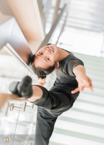 Анджелия Ван, родом из Чикаго, использует перила стеклянной лестницы театра в качестве станка для разминки!