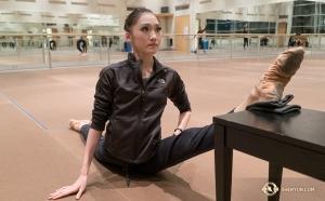 空中で180度(またはそれ以上)の開脚をするために、ダンサーはステージに上がる前にさらに脚を開くストレッチをする。ピアノの椅子を利用するダンサー、ジャスティナ・ワン(撮影:打楽器奏者、ティファニー・ユ)