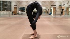 Główna tancerka Evangelina Zhu rozgrzewa się łamiąc się w pół, (fot. perkusistka Tiffany Yu)