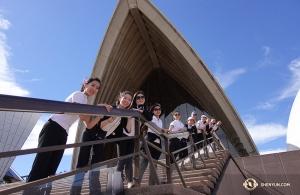 與此同時,神韻國際藝術團正造訪澳大利亞。藍天白雲下,神韻舞蹈演員們在悉尼歌劇院前依欄拾階而立,悉尼我們來了!(攝像:神韻天幕師李艾妮)