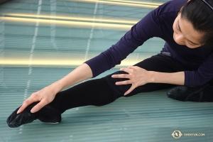 Efter lite sightseeing är det dags att stretcha. Solistdansaren Linjie Huang börjar och ägnar särskild uppmärksamhet åt sina utåtriktade tår. (Foto av projektionist Annie Li)