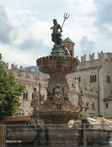 Фонтан Нептуна в центре площади Пьяцца-дель-Дуомо в Италии. Римский бог морей с трезубцем наблюдает за оживлённым движением на главной площади Тренто.