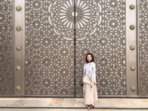 La voici devant un ensemble de portes finement sculptées.