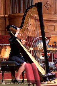 Harfistka Shirley Guo wykorzystuje wolnąchwilę przed koncertem, by dostroić struny.