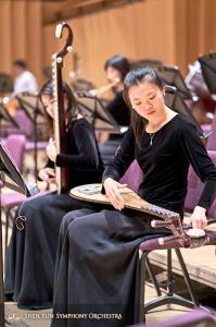 Grająca na pipie Miao-Tzu Chiu dostraja swój instrument uprzednim założeniu nowej struny.