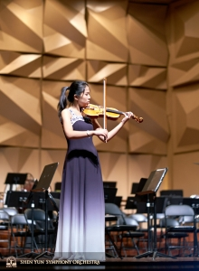 Already changed for the performance, violin soloist Fiona Zheng takes advantage of a final opportunity to practice on stage.