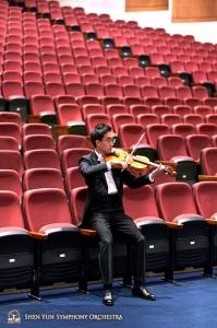 Violist Jeff Lai warmt op tussen de stoelen in de zaal van Taoyuan's Zhongli Arts Hall.
