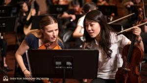 Eerste violiste Rachel Chen (r) en assistent eerste violiste Paulina Cha bespreken het nieuwe encore stuk, toegevoegd voor ons enthousiaste Taiwanese publiek.