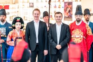 Il primo fagotto AleksanderVelichko (a sinistra) e il trombonista basso PavloBaishev posano insieme a modelli coreani che indossano l'abbigliamento regale tradizionale