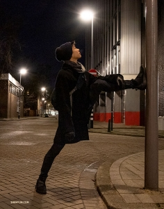 It's true, dancers will stretch anywhere. Roy Chen pauses while taking an evening stroll through Rotterdam. (Photo by Nick Zhao)