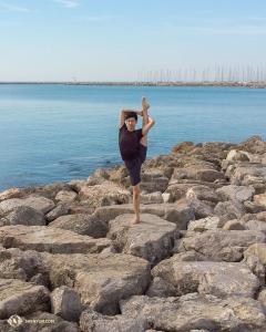 Tancerz Scott Xu prezentuje pozycję stabilnego trzymania nogi w pionie (chao-tian-deng) na skałach. (Tancerz Andrew Fung)