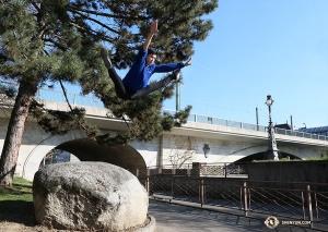 Tancerz zeskakuje z głazu w Genewie – trzymajcie kciuki żeby miękki wylądował. (Nick Zhao)