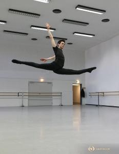 W teatrze, w sali przeznaczonej do ćwiczeń, tancerz Peter Kruger rozgrzewa się, wykonując wyskoki ze szpagatem. (Photo by Nick Zhao)