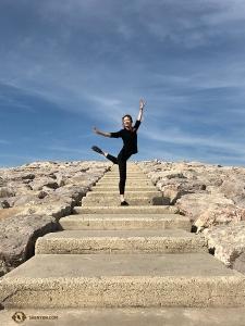 Tancerka Daoyong Zheng pozuje na kamiennych schodach nieopodal plaży. (Kinooperatorka Annie Li)