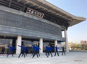 由於清州藝術中心內的空間有限,排練被移到外面的廣場。我們正在劇院的反光玻璃門前同步我們的動作——它們當鏡子用還相當不錯呢!