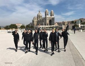 Tancerze radośnie spacerują w Marsylii, w tle katedra.
