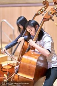 バス奏者の二人:張覚暁(左)とクロエ・チャン。トロントのロイ・トムソン・ホールでの神韻交響楽団の演奏会前のウォーミングアップ。
