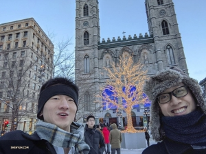 Ben Chen takes a selfie of himself with fellow dancer Jun Liang and a well-lit holiday tree.
